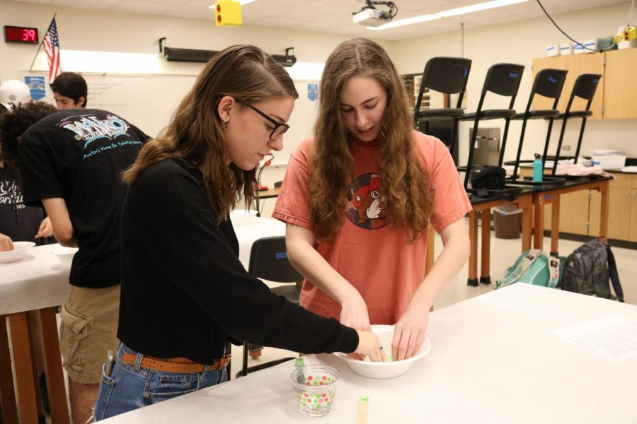 """Bailey Armosky '20 and Sarah Armosky '20  knead the ingredients with their hands to make oobleck. Sarah has been a member of Science Club since last year. """"I joined [Science Club] because Kate [the president] said that we would get to do some fun experiments and learn things."""""""