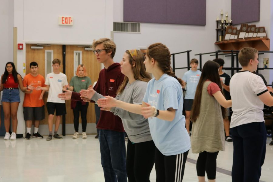 Ian Webster '20, Ashley Howell '21, and Rachel Rusch '20 help lead the choir in an icebreaker. This activity helped choir members bond with each other.