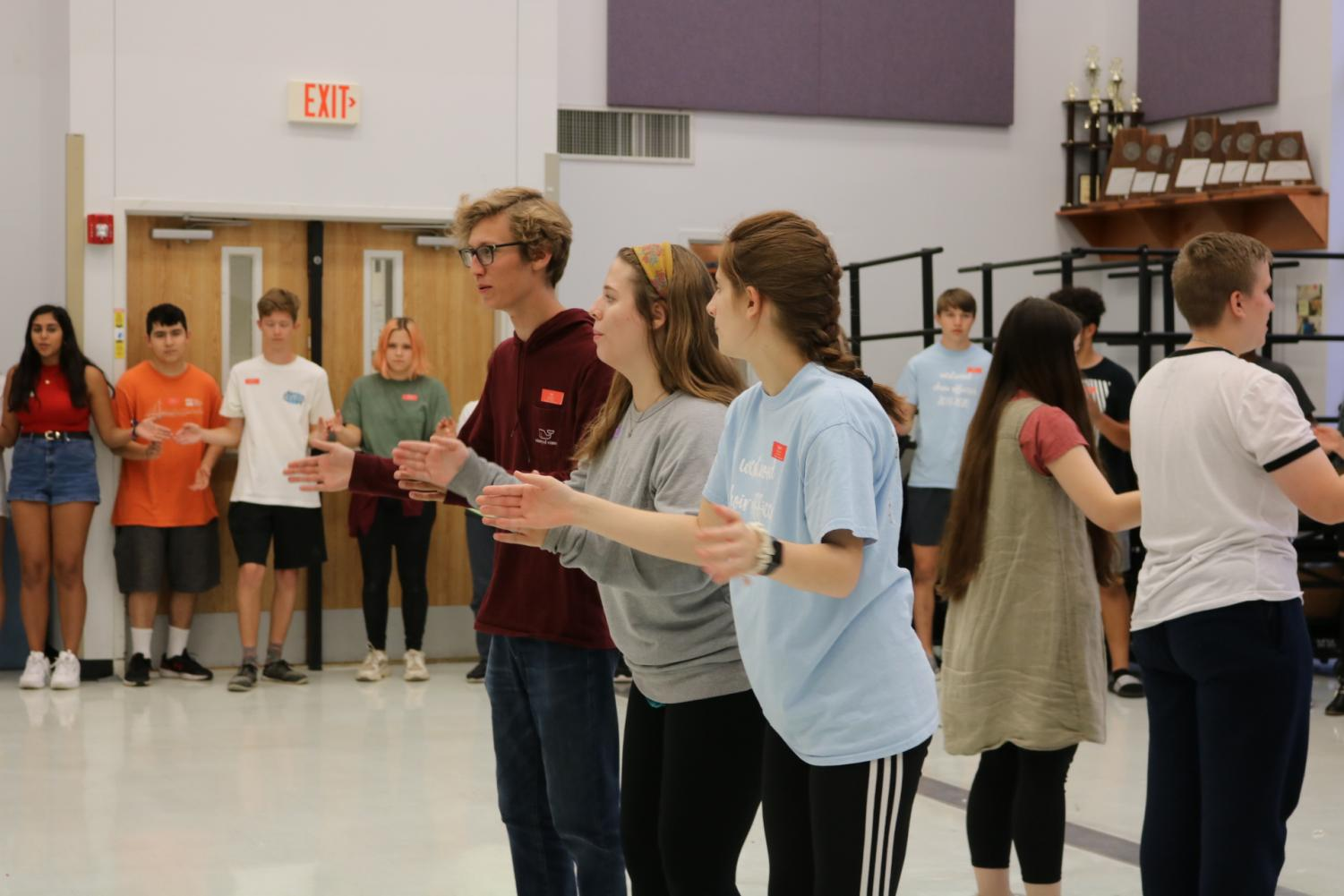 Ian+Webster+%2720%2C+Ashley+Howell+%2721%2C+and+Rachel+Rusch+%2720+help+lead+the+choir+in+an+icebreaker.+This+activity+helped+choir+members+bond+with+each+other.+%22The+game%2C+I+originally+learned+it+in+theatre+but+we%27ve+been+doing+it+at+choir+camp+since+my+freshman+year.+It%27s+just+a+really+fun+game+because+everyone+messes+up%2C+but+no+one+gets+singled+out%2C%22+Rusch+said.