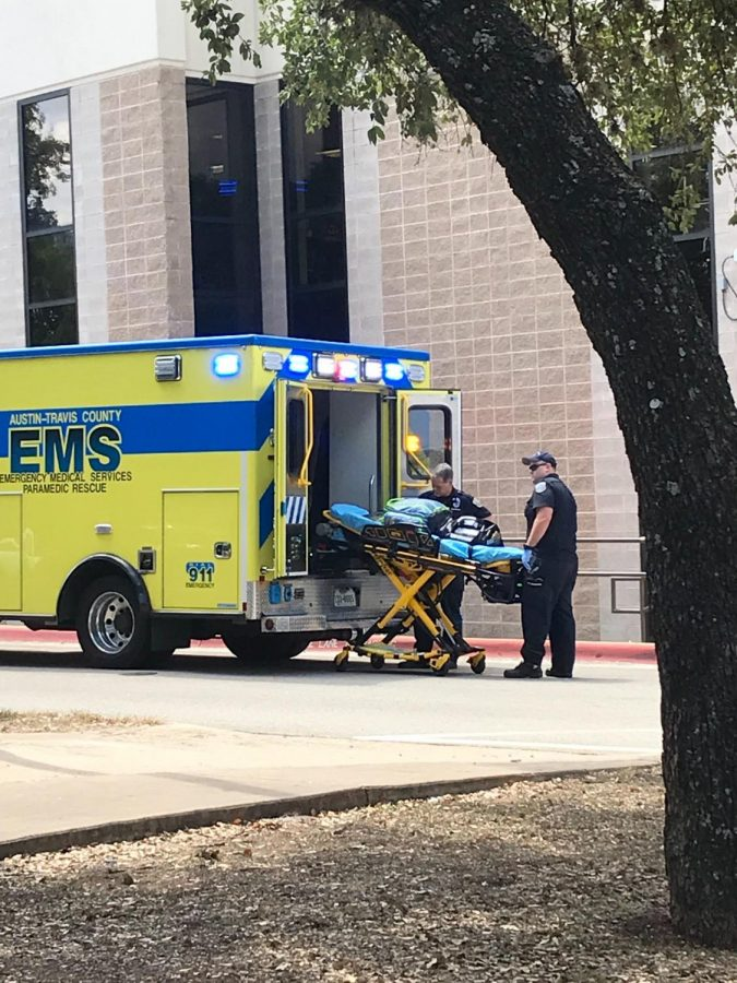 EMTs unload a gurney from an ambulance in front of Westwood High School on Sept. 9.
