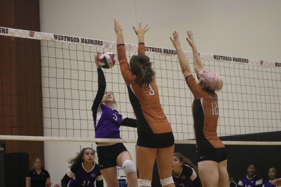 Ella Wood '23 and Kylie Wardlow '23 jump and block the ball. Wardlow played as a middle blocker and Wood played as an outside hitter.
