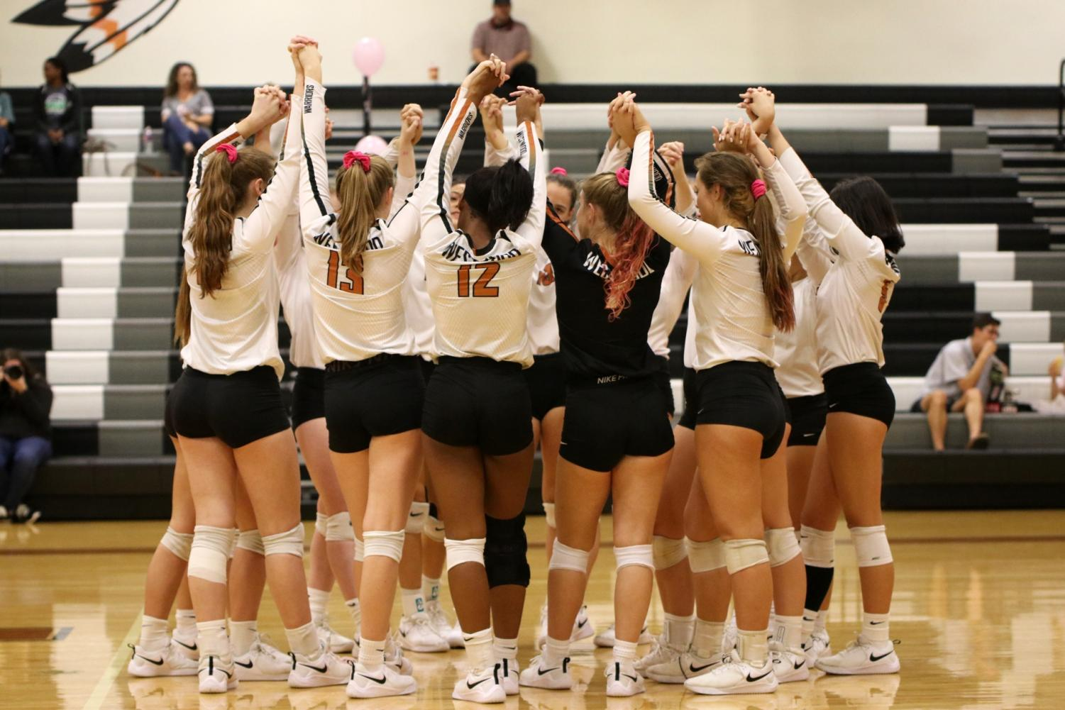 The+Lady+Warriors+raise+their+arms+in+their+pre-game+ritual.+The+Lady+Warriors+played+the+McNeil+Mavericks+in+the+Dig+Pink+game+which+raised+money+for+breast+cancer+research.