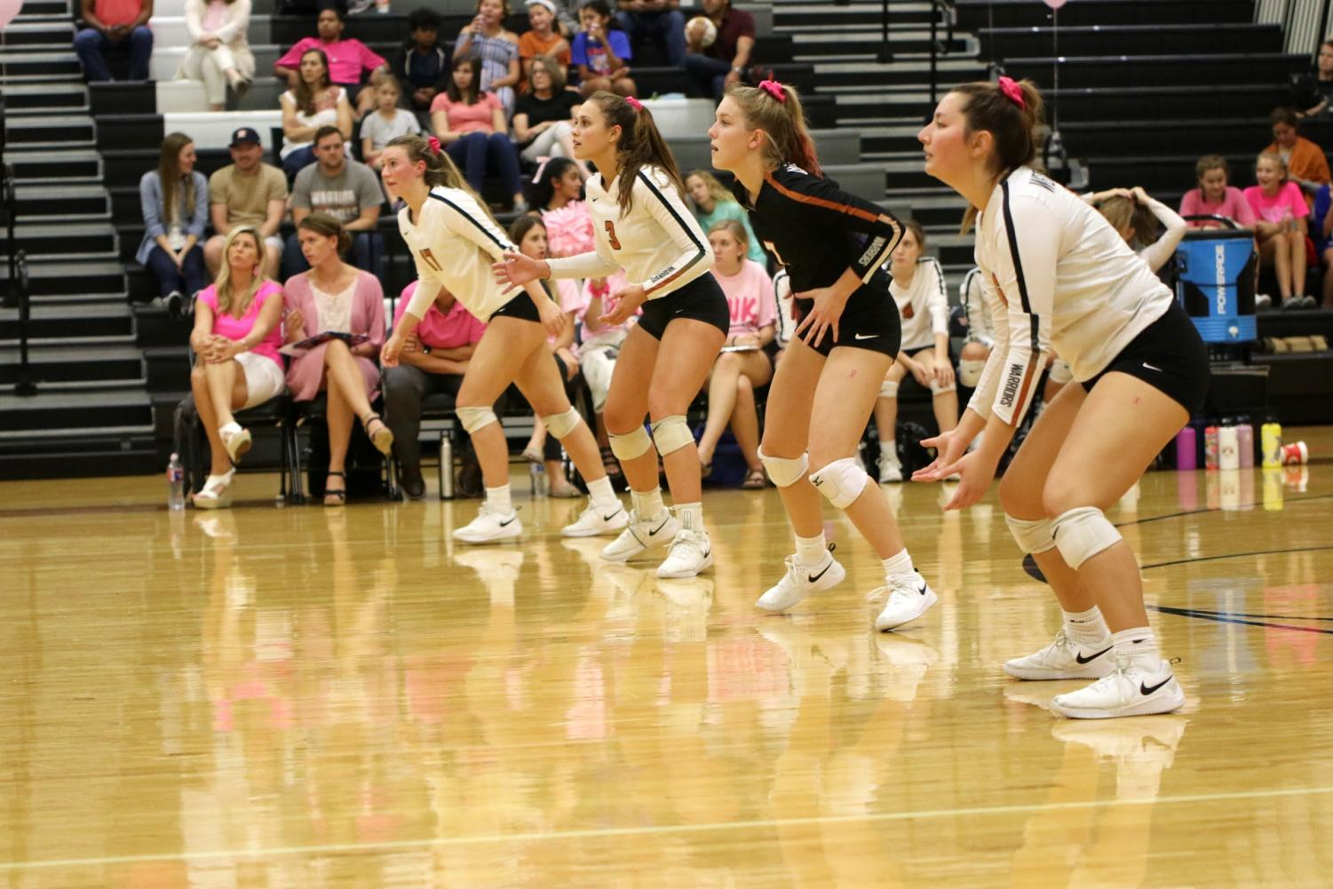 Juniors+Kenzie+Beckham+and+Abby+Gregorczyk+stand+alongside+seniors+Maddie+Gillispie+and+Abi+Rucker+before+McNeil+serves+the+ball.+The+Lady+Warriors+wear+pink+scrunchies+as+a+symbol+of+breast+cancer+awareness.
