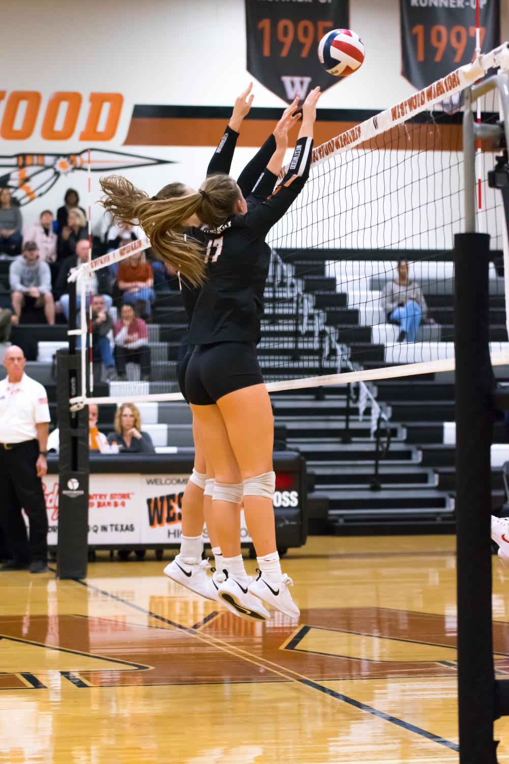Jumping+in+unison%2C+Audrey+Quesnel+%2720+and+Kenzie+Beckham+%2721+block+the+oncoming+ball.+The+Lady+Warriors+ended+up+earning+the+point+and+kept+their+early+on+lead+during+the+first+set.