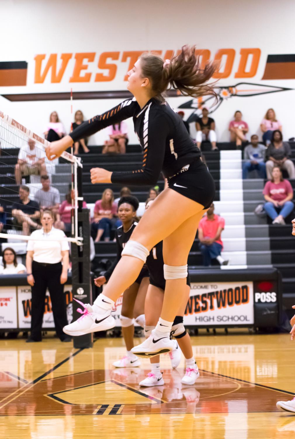 Jumping+in+the+air%2C+outside+hitter+Kenna+Williams+%2722+spikes+the+ball+over+the+net.+The+Lady+Warriors+won+the+point%2C+keeping+their+lead+over+the+Mavericks+during+the+second+set.