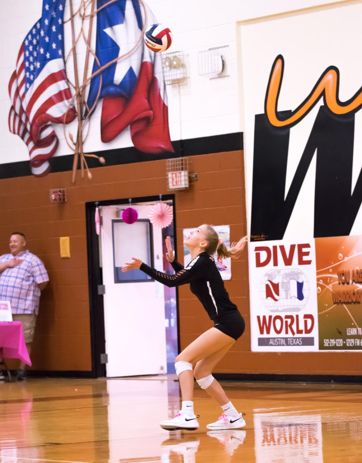 With+the+ball+in+the+air%2C+Claire+Delane+%2723+eyes+it+carefully+to+execute+the+serve.+Delane+made+several+crucial+serves+throughout+the+game.