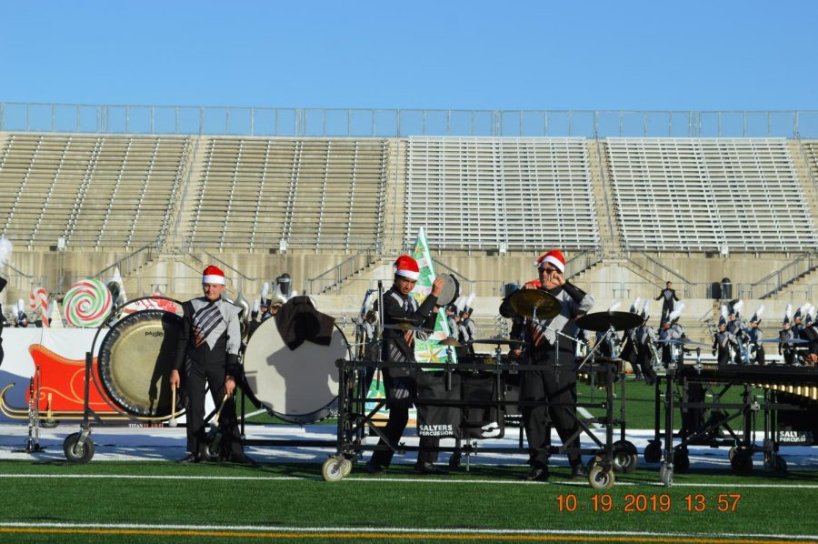 Adorned with Santa hats, percussion players play snare and cymbals.