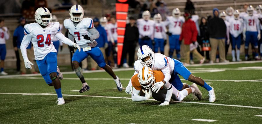 Player Player '00 gets tackled by a the Leander defense. Despite of the hard tackle, Player was able get past 10 yards.