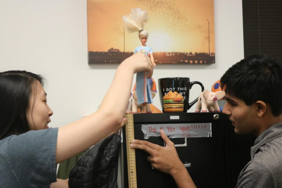 Sunny Lee '21 and Harshil Shah '21 set the Barbie on top of a cabinet and hold a yardstick to measure how far their doll will go.