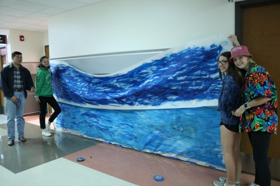 Members of choir hold up their poster, which they have painted blue to match the theme of the rest of the hallway. That hallway was filled with blue streamers, wave-like posters, and other water representing decorations.