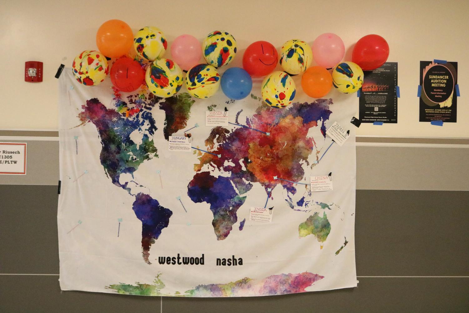 Westwood+Nasha%2C+the+Bollywood+club%2C+created+a+poster+depicting+their+choice+of+gymnastics+for+the+homecoming+theme+of+Olympics.+They+made+a+poster+of+the+world+with+colorful+balloons%2C+cards+that+talk+about+famous+gymnasts%2C+and+other+decorations.