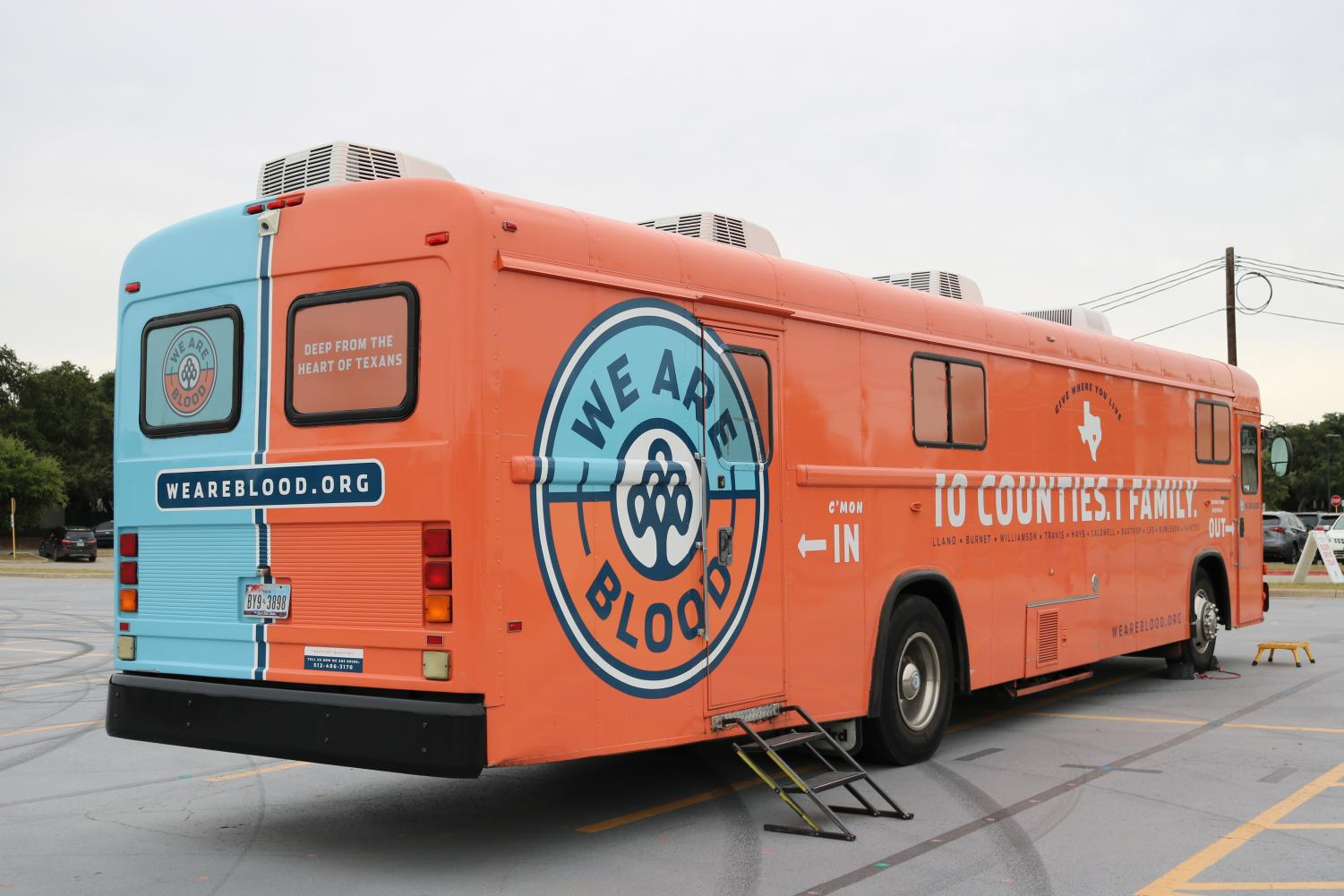 The+We+Are+Blood+bus+sits+in+the+Westwood+Band+practice+lot+with+participants+donating+blood+inside.