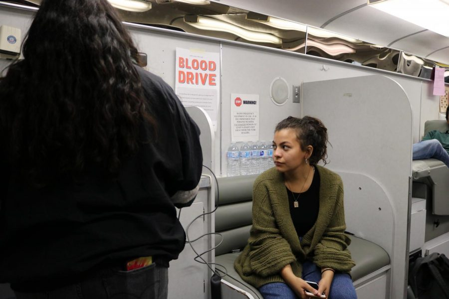Heather Lobera '20 patiently waits for a blood drive helper to ask her questions before she can donate blood.