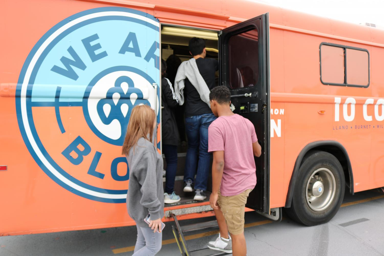 Students+eager+to+donate+blood+climb+into+the+crowded+bus+where+they+await+their+turn.