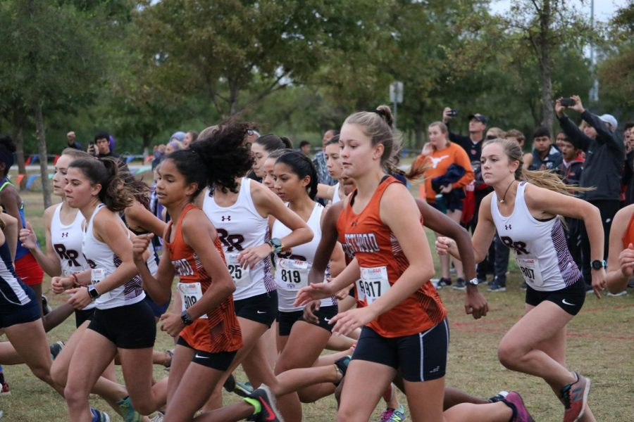 The Varsity Girls rush ahead of other runners at the start of the race.