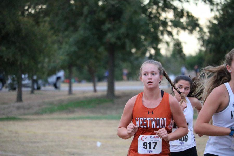 Samantha Newlin '22 runs alongside two Vandergrift runners.