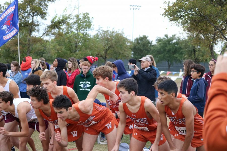 The Varsity Boys get set to start the race right before the pistol gets shot.