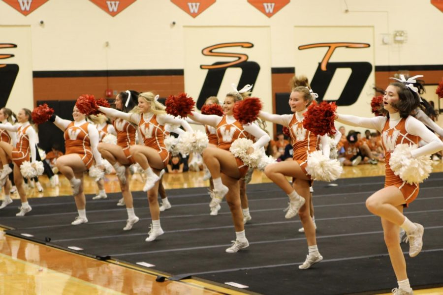 Cheerleaders are hyped up as they welcome the students entering the gym for the homecoming pep rally. The cheerleaders had the drum line backing them up and supplying them with fun energetic beats to move and perform to. With smiling faces, the cheerleaders made sure to make people feel welcome at this event.