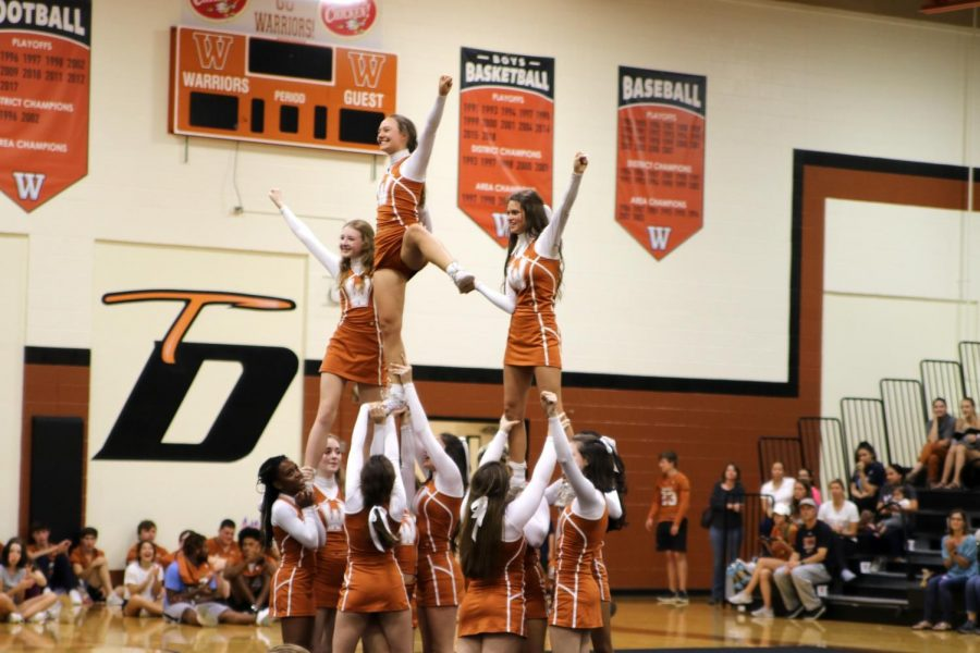 Cheer team impresses the crowd with their stunts. The cheerleaders truly worked together and performed as a team, and performed gracefully and safely.