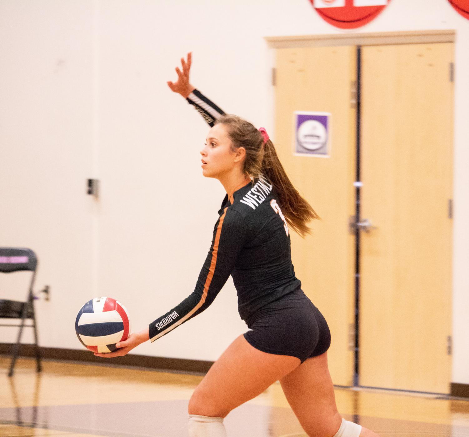 Holding+the+ball%2C+Abby+Gregorczyk+%2721+prepares+to+throw+the+ball+in+the+air+for+a+serve.+This+play+ended+with+the+Warriors+winning+the+point.
