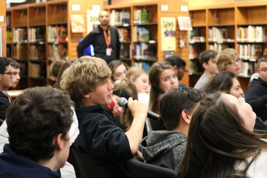 A student asks the author a question. Students were asking questions about 'Bronx Masquerade,' a book they had read in class.