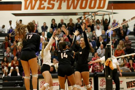 The team celebrates after scoring a point. This was near the end of the third set, so tensions were high.