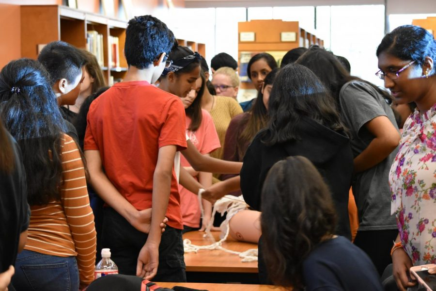 At the end of the session, students gather around to try out wound packing. UT students gave tips to participants and answered questions once the lesson was over.