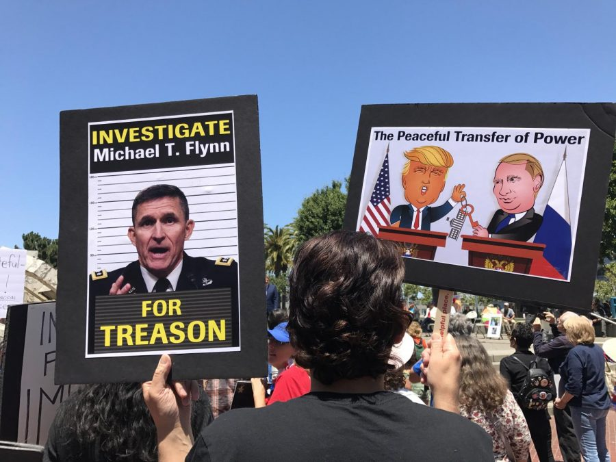 At the Impeachment March on July 2, 2017, a participant holds up signs protesting the Trump administration's relationship with Russia.