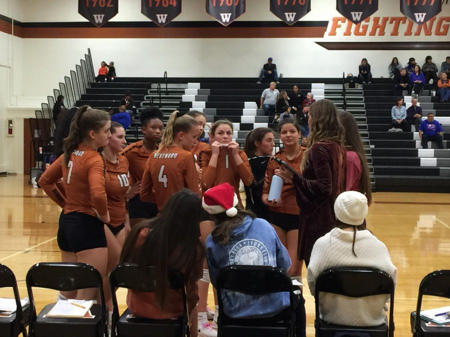 The Lady Warriors receive advice from Coach Amber Hall after winning the first set. The team won the first set 25-12.
