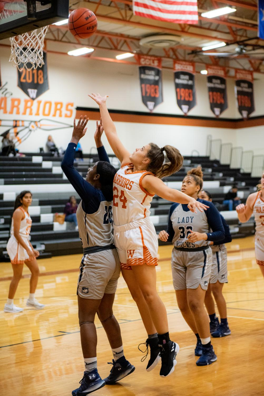 Jumping%2C+Kooper+Giles+%2720+rebounds+her+missed+shot.+After+the+rebound+the+team+was+able+to+get+another+chance+at+the+shot+and+ended+up+shooting+a+two-pointer.