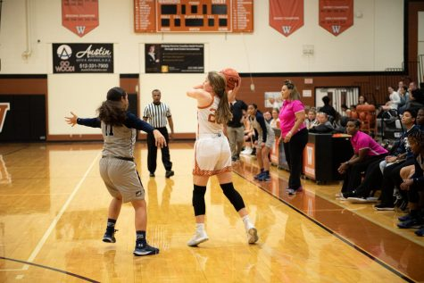 Peyton Halley '21 throws the ball above the defensive player. Halley, a junior, plays the position of a guard on the team.