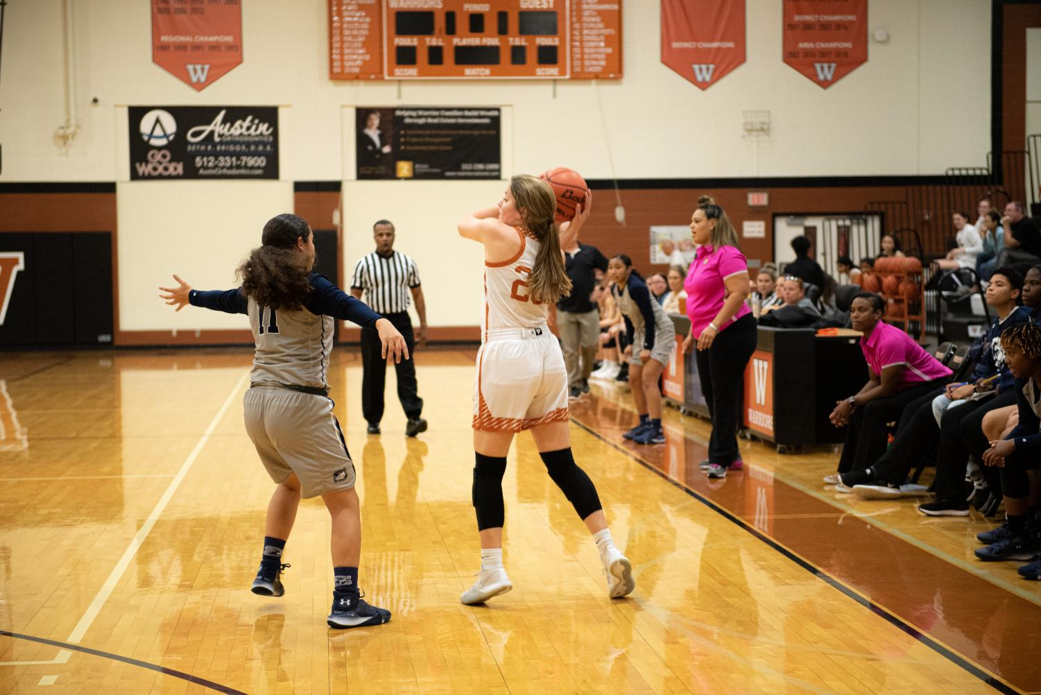Peyton+Halley+%2721+throws+the+ball+above+the+defensive+player.+Halley%2C+a+junior%2C+plays+the+position+of+a+guard+on+the+team.