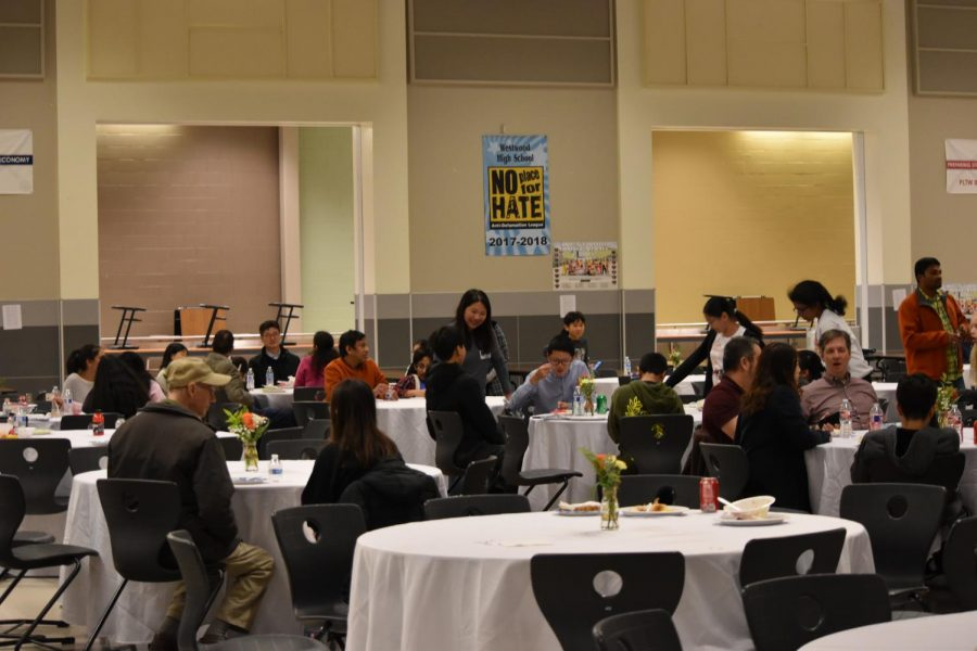 Students and parents gather at different tables to chat. Food was provided by parents for attendees to eat as they socialized.