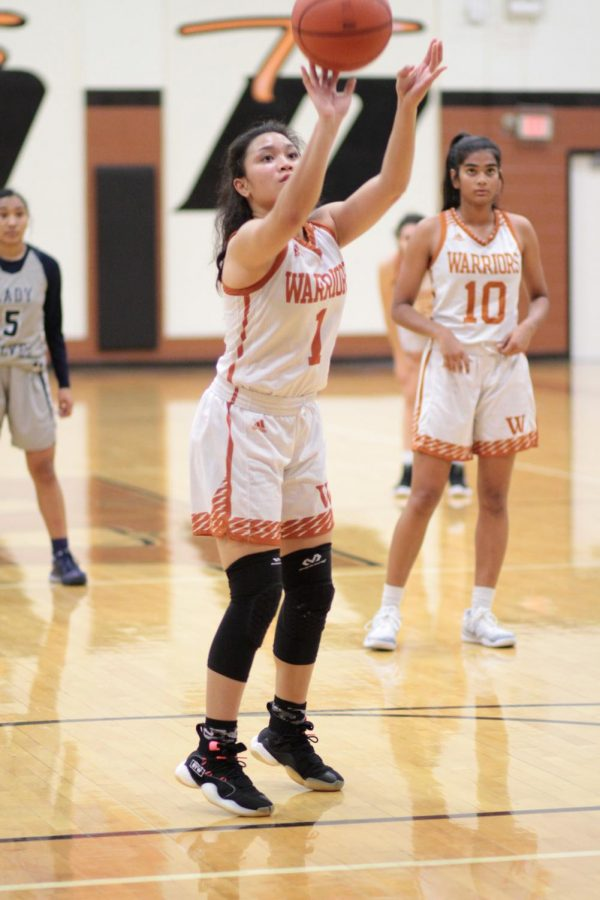 Reaching up, Annalise Galliguez '20 takes one of two shots from the free throw line. These shots ended up getting Westwood two more points.