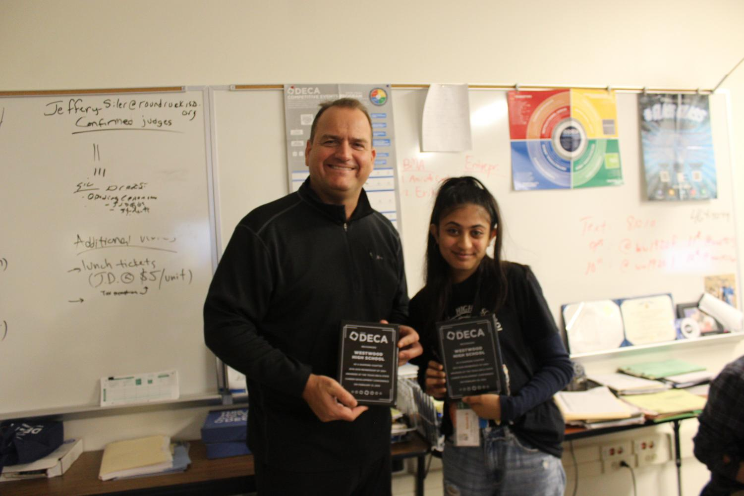 Mr.+Jeff+Siler+and+Sakshi+Dhavalikar+%2721+pose+with+the+DECA+plaques+that+were+used+to+show+the+8th+graders+how+big+our+DECA+chapter+has+grown+and+how+well+it%27s+done.++Ambassadors+encouraged+them+to+join+career-related+clubs+to+help+them+gain+more+knowledge+and+soft+skills.