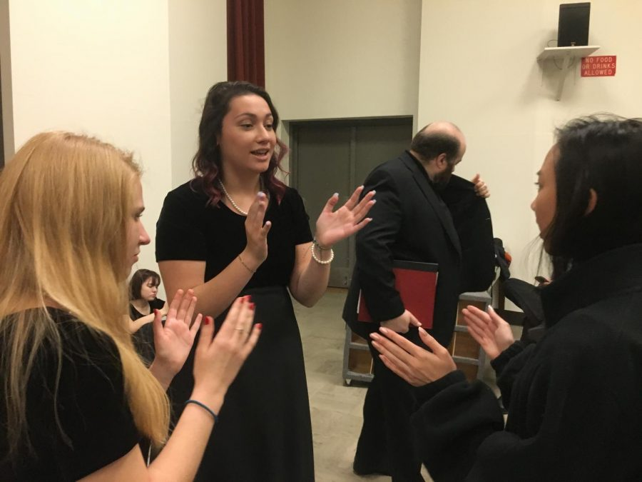 Choir students Sarah Sherwood '20, Violet Rogers '20, and Elsa Hughes '20 bond after rehearsal. They relaxed by playing a hand clapping game.