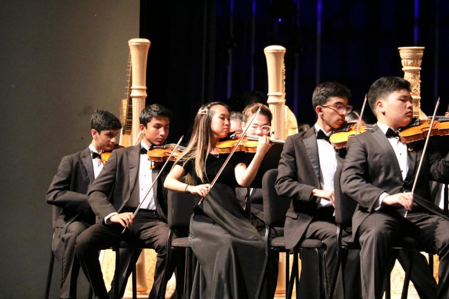 Symphony orchestra first violinists demonstrate stellar technique in the lively Carnival Overture op. 92 by Antonin Dvorak. Principal player Elliot Kim '21 performed a short solo.
