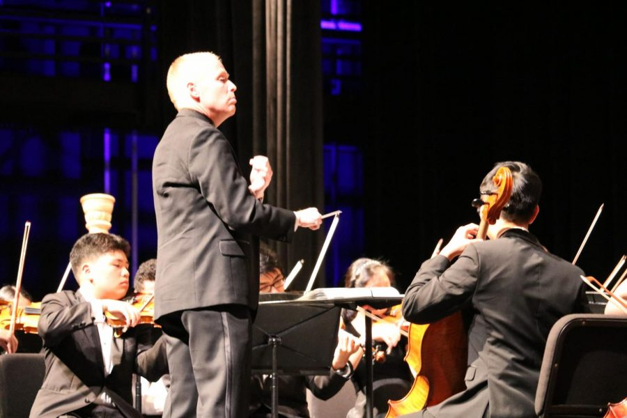 Director Joshua Thompson conducts the symphony orchestra during their performance of Across the Stars (Love Theme from Star Wars: Episode III) by John Williams