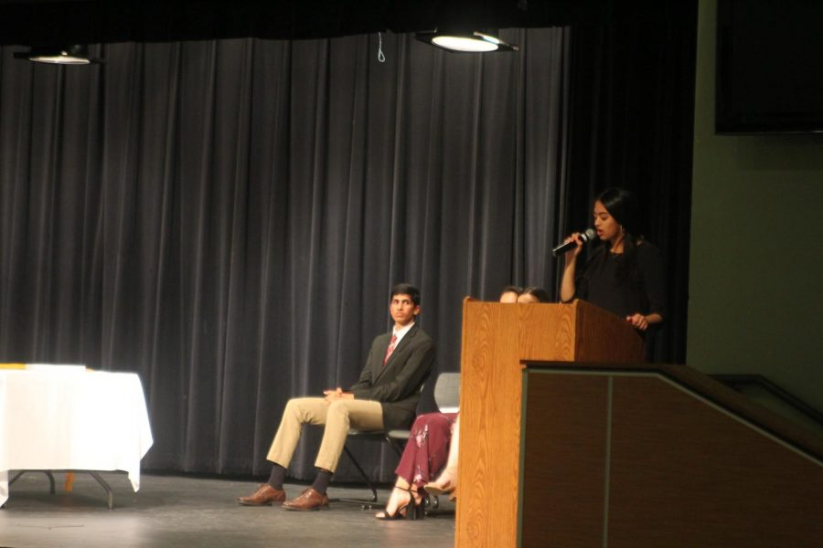 Sruthi Ramaswamy '20 speaks to the new inductees while Vice President Anish Maddipotti '20 looks on. Ramaswamy serves as the historian for the society.