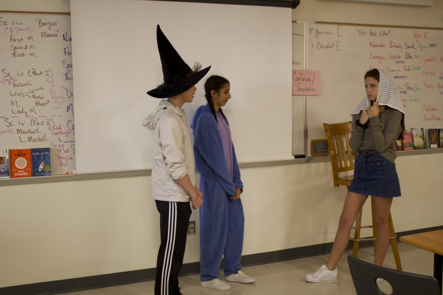 Inshal Khawaja '22 and Schuylar Salemme '22 listen as Ryan Tay '22 recites a line from Macbeth. The sophomores are playing the three witches that represent the supernatural forces at work in the play.