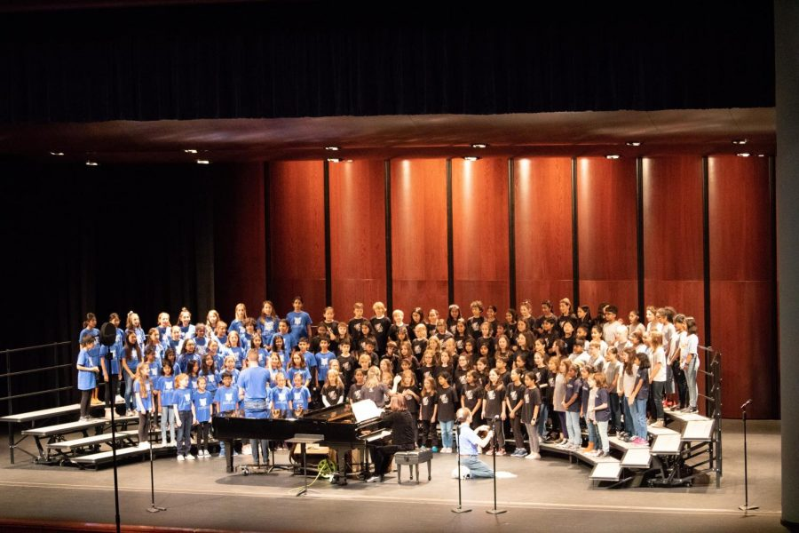 Choirs from Anderson Mill, Canyon Creek, and Caraway Elementary perform on stage.