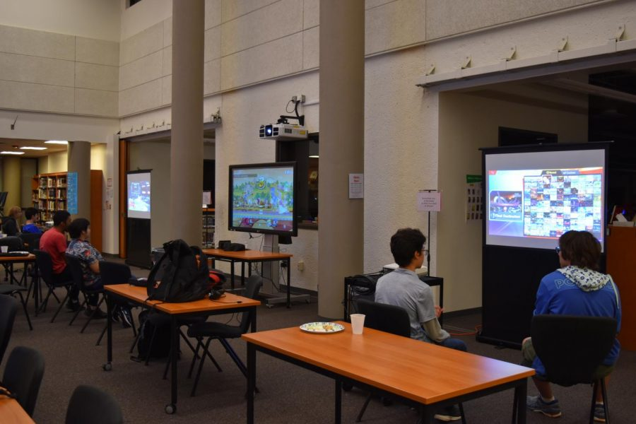 Players sit in front of projectors to compete. Three projectors and a computer were set up before the tournament to display the games.