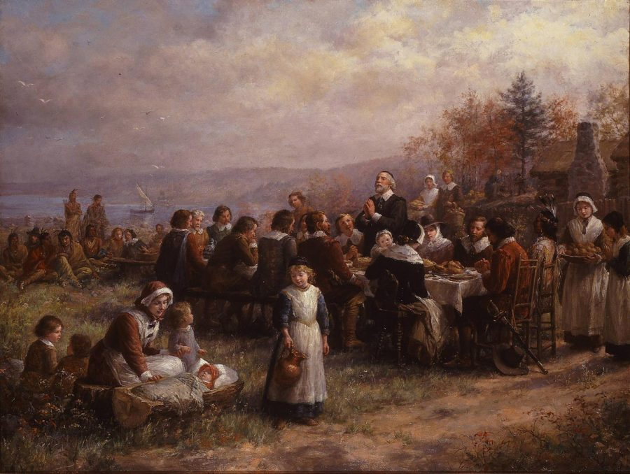 Native+Americans+and+Pilgrims+share+a+feast+at+a+depiction+of+the+first+Thanksgiving.+The+first+Thanksgiving+was+held+in+October+1621.