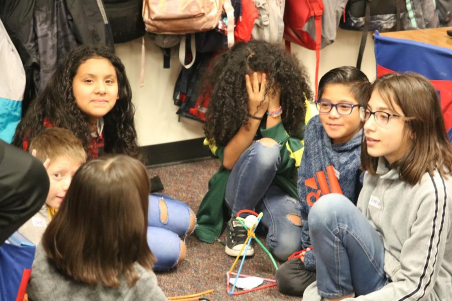 Anderson Mill students work together to balance a golf ball on straws and pipe cleaners for the 'Tall Tower' challenge.