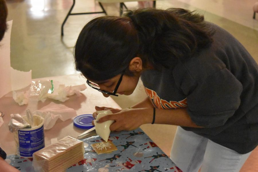 Vani Shah '20 draws a snowflake on a graham cracker with icing. Along with other ambassadors, she participated in a gingerbread house competition.