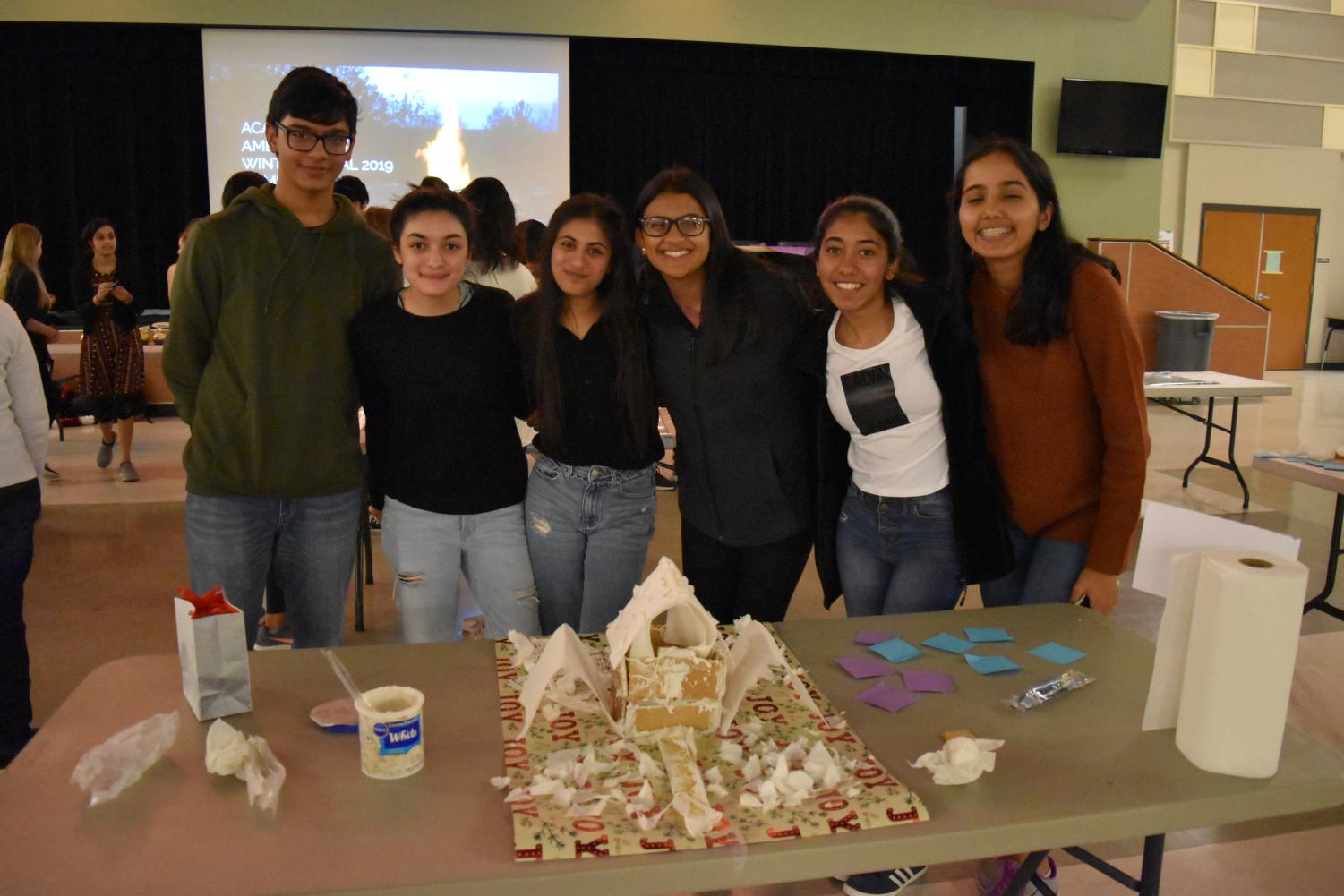 A+team+in+the+gingerbread+house+contest+poses+with+their+finished+product.+After+voting+from+all+the+ambassadors%2C+the+team+was+crowned+the+winner+of+the+competition.