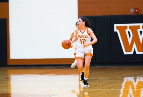 Dribbling down the court, power forward Desi Davalos '22 scans for teammates to make a pass to. Despite efforts from the team, the Lady Warriors were unable to pull ahead of the Raiders during the first half.