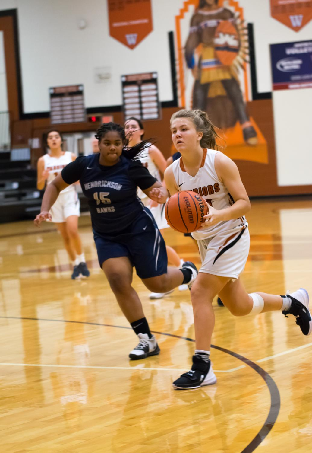 With+a+defensive+player+on+her+right%2C+Atlee+Olofson+%2723+dribbles+the+ball.+Olofson+attempted+to+make+a+2-pointer%2C+but+missed.