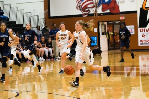 Emma Goolsbey '21 dribbles the ball down the court. Goolsbey would score several 2-pointers throughout the game.