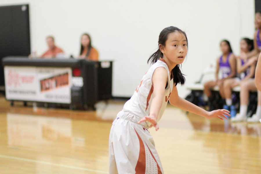 Arms out, Olivia Yang '23 looks at the oncoming Raiders. Yang was trying to block the Raiders from scoring.